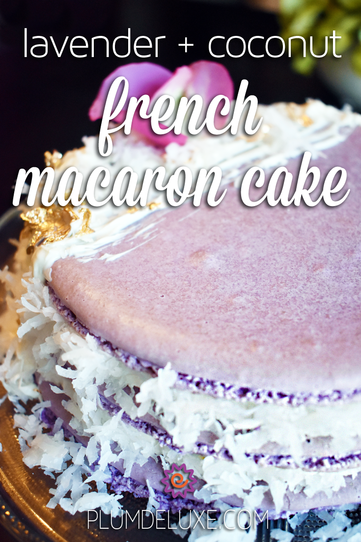 Photo of a purple french macaron cake decorated with shredded coconut, buttercream, rose petals, and edible gold leaf. The overlay text reads: lavender + coconut french macaron cake.