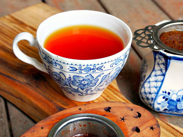 A white and blue floral teacup full of red rooibos tea sits on a wooden table next to two other cups of tea with infusers in them.