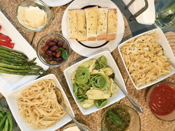 Overhead view of three square dishes filled with pasta and surrounded by dishes of toppings and sauces.