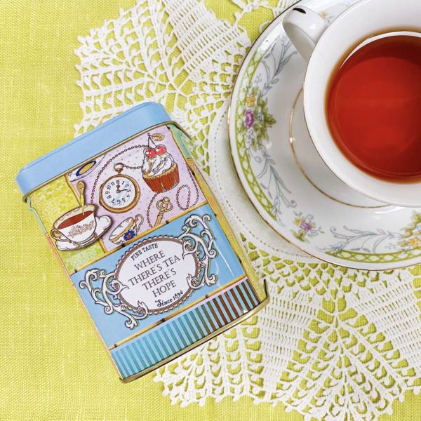 Overhead view of a tea-themed blue tea tin next to a white and floral teacup and saucer. They are arranged on a green cloth overlain with a white crochet doily.