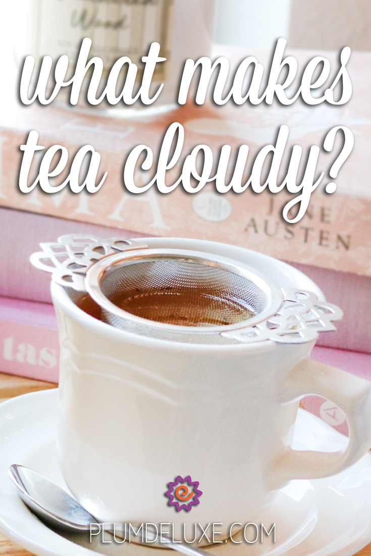 A white teacup and saucer with a victorian style metal infuser sits in front of a stack of books. The overlay text reads: what makes tea cloudy?