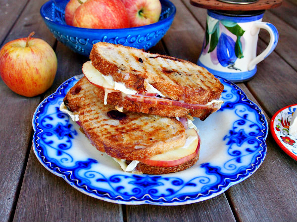 Two ham, brie, and apple tea sandwiches are arranged on a blue and white plate. Behind them can be seen a red apple, a blue bowl of more apples, and a blue and white floral mug with a wooden tea infuser.