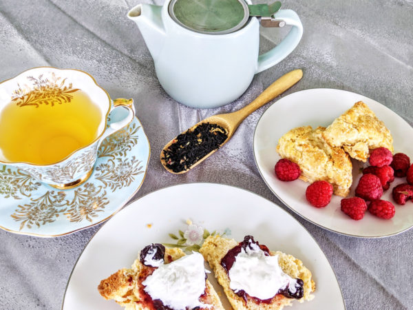 A wooden scoop of loose leaf tea is surrounded by two plates of scones with fruit and clotted cream, a white and gold cup of tea, and a white teapot on a silver cloth.