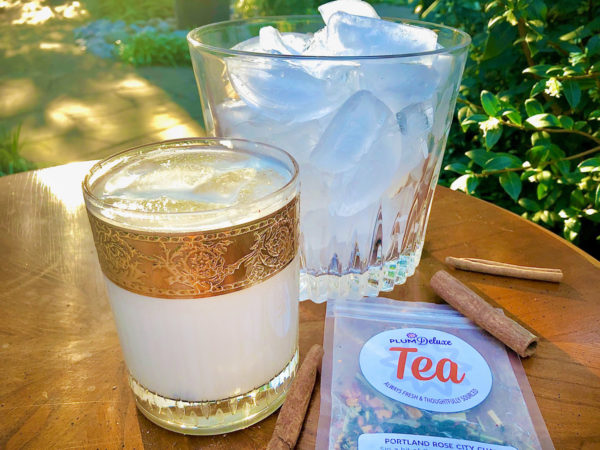 A clear glass with gold filigree design on the rim is filled with iced chai tea latte. Next to it is a larger glass of ice cubes, a package of Plum Deluxe loose leaf chai tea, and cinnamon sticks on a wooden table outside.