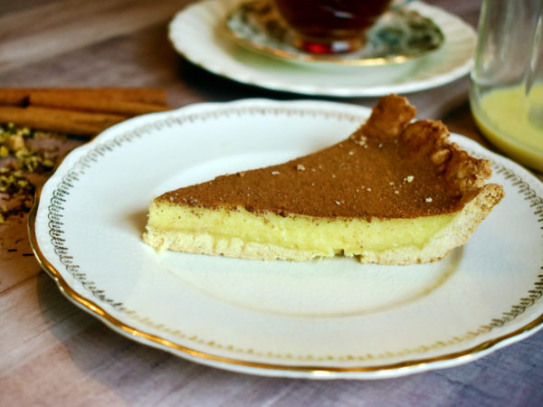 A slice of milk tart sits on a white plate on a wooden table. Cinnamon sticks and a cup of tea can be seen in the background.