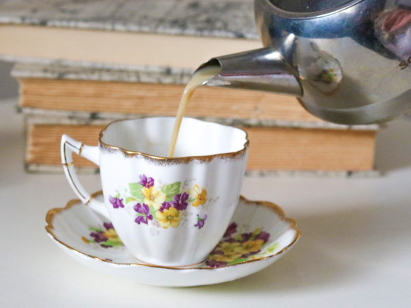 A metal teapot pours royal milk tea into a white teacup with purple and yellow violets on it. A stack of books is in the background.