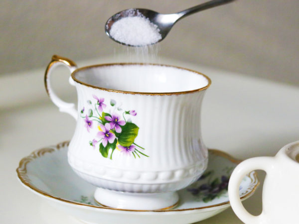 A silver spoon pours sugar into a white teacup with a purple flower on it.