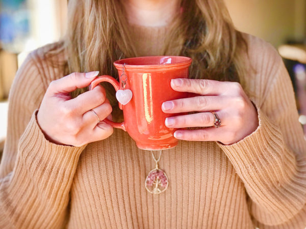 A femme person with light brown hair wearing a ribbed tan sweater holds an orange mug of tea in their hands.