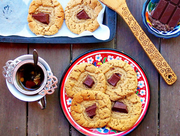 Overhead view of a red floral plate full of chocolate almond cookies on a wooden table. Surrounding it are a cup of tea, a tray with more cookies, a wooden spoon, and a dish of chocolate chunks.