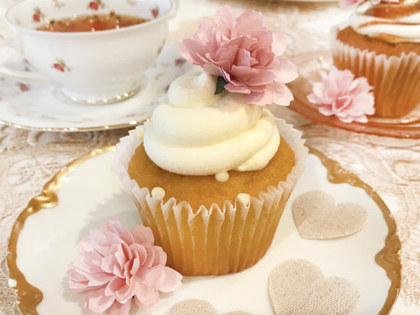 A vanilla cupcake with white buttercream frosting is decorating with pink paper flowers. It sits on a white plate with gold edging. A cup of tea can be seen in the background.