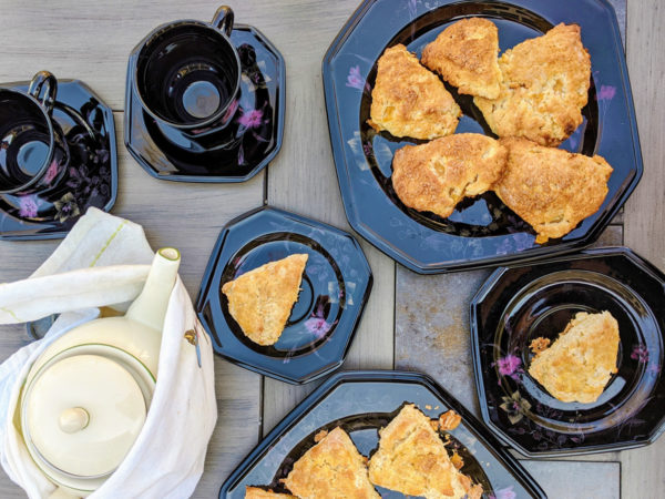 Overhead view of black lacquered plates full of coconut mango scones, matching black teacups, and a white teapot.