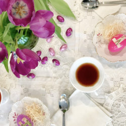 Overhead view of a tablescape for an Easter tea party, including purple tulips, egg candies, egg place holders, white lace linens, and white teacups of tea.