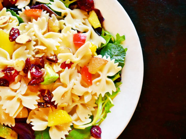 A white plate holds a colorful salad of bow tie pasta, red pepper, avocado, mango, and plum.