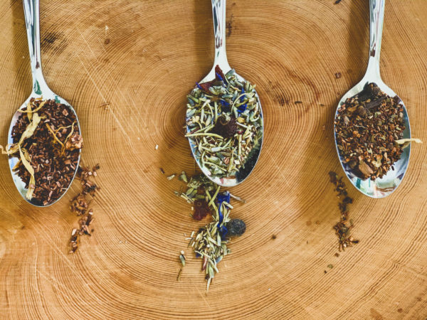 Three silver teaspoons with different kinds of loose leaf herbal teas are arranged in a row on a wooden board.