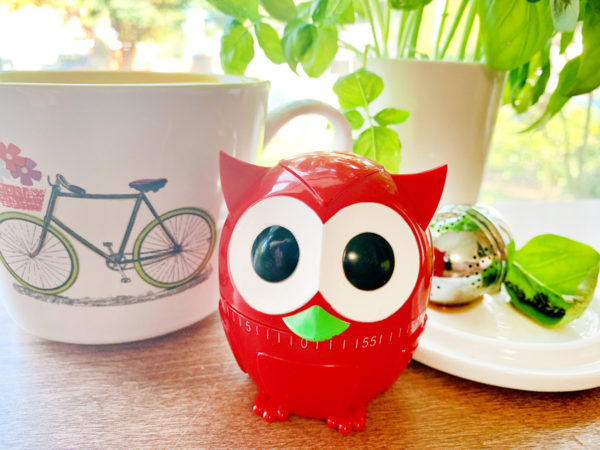 A red owl timer sits in front of a white mug with a bicycle on it and a small white plate holding a stainless steel tea ball and a green leaf. In the background is a white pot full of basil.