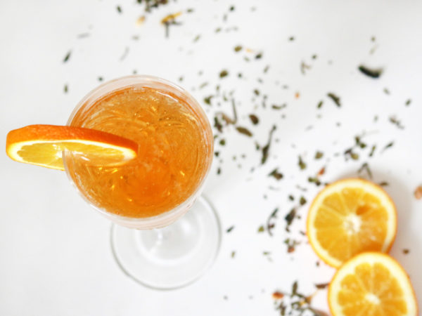 Overhead view of a champagne flute full of bubbly orange liquid and garnished with an orange slice. It stands on a white table surrounded by tea leaves and two orange slices.