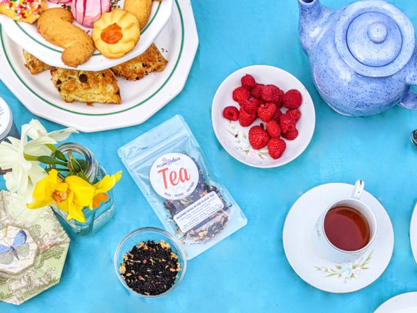 A tiered serving tray full of cookies and scones, a vase of daffodils, and floral print box, a package of Plum Deluxe loose leaf tea, and a dish of loose tea leaves are arranged on a bright blue cloth.