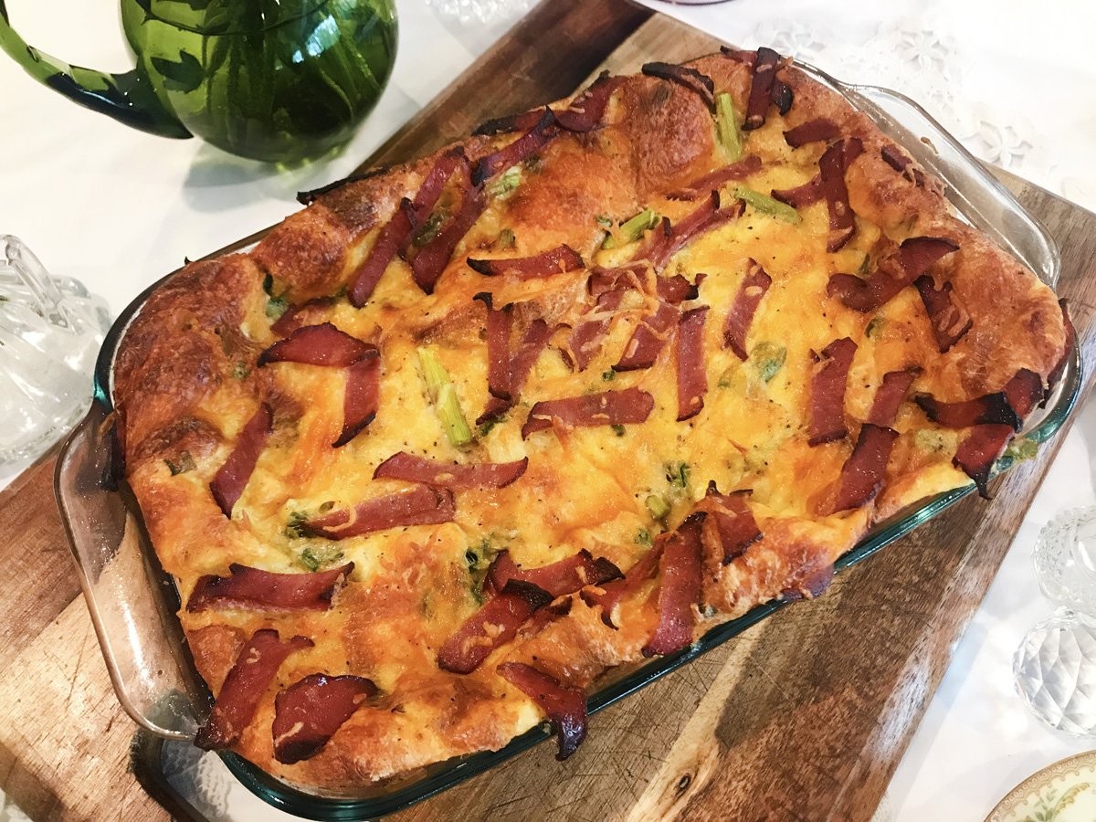 A large baking dish holding a brioche bread pudding sits on a wooden board on a white tablecloth.