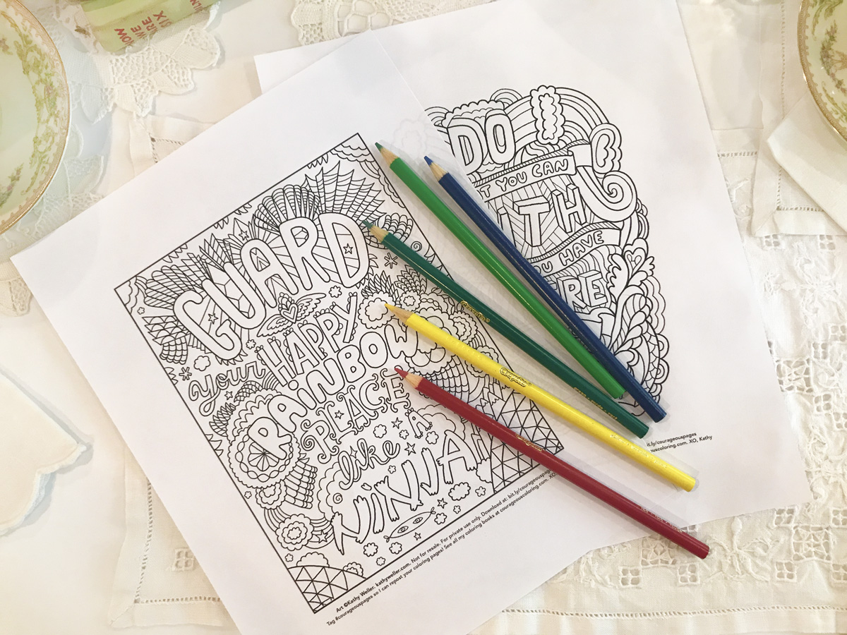 Coloring pages and colored pencils sit on a white lace tablecloth.