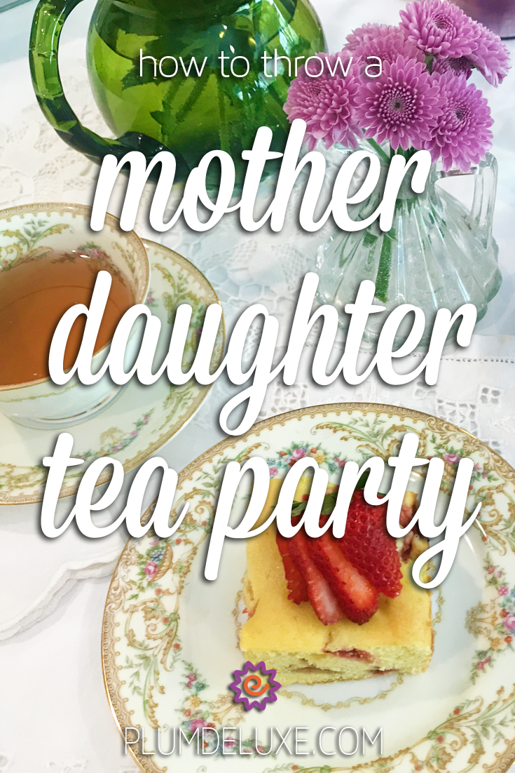 A square of strawberry cake with a fresh strawberry on top sits on a white plate with a floral edging. Next to is is a matching teacup and saucer of tea and a vase of purple flowers. The overlay text reads: how to throw a mother daughter tea party.