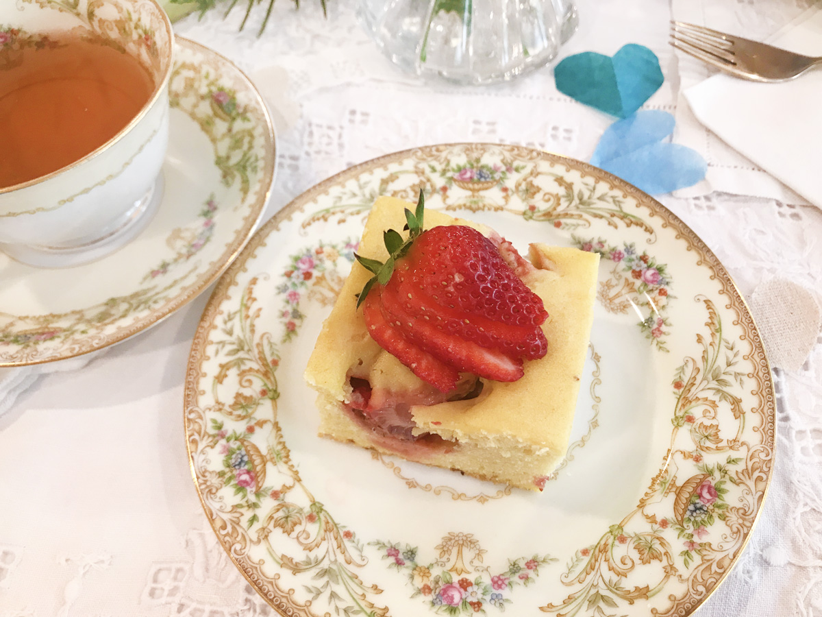 A square of strawberry buckle cake with a fresh strawberry on top sits on a white plate with a floral edging. Next to is is a matching teacup and saucer of tea.