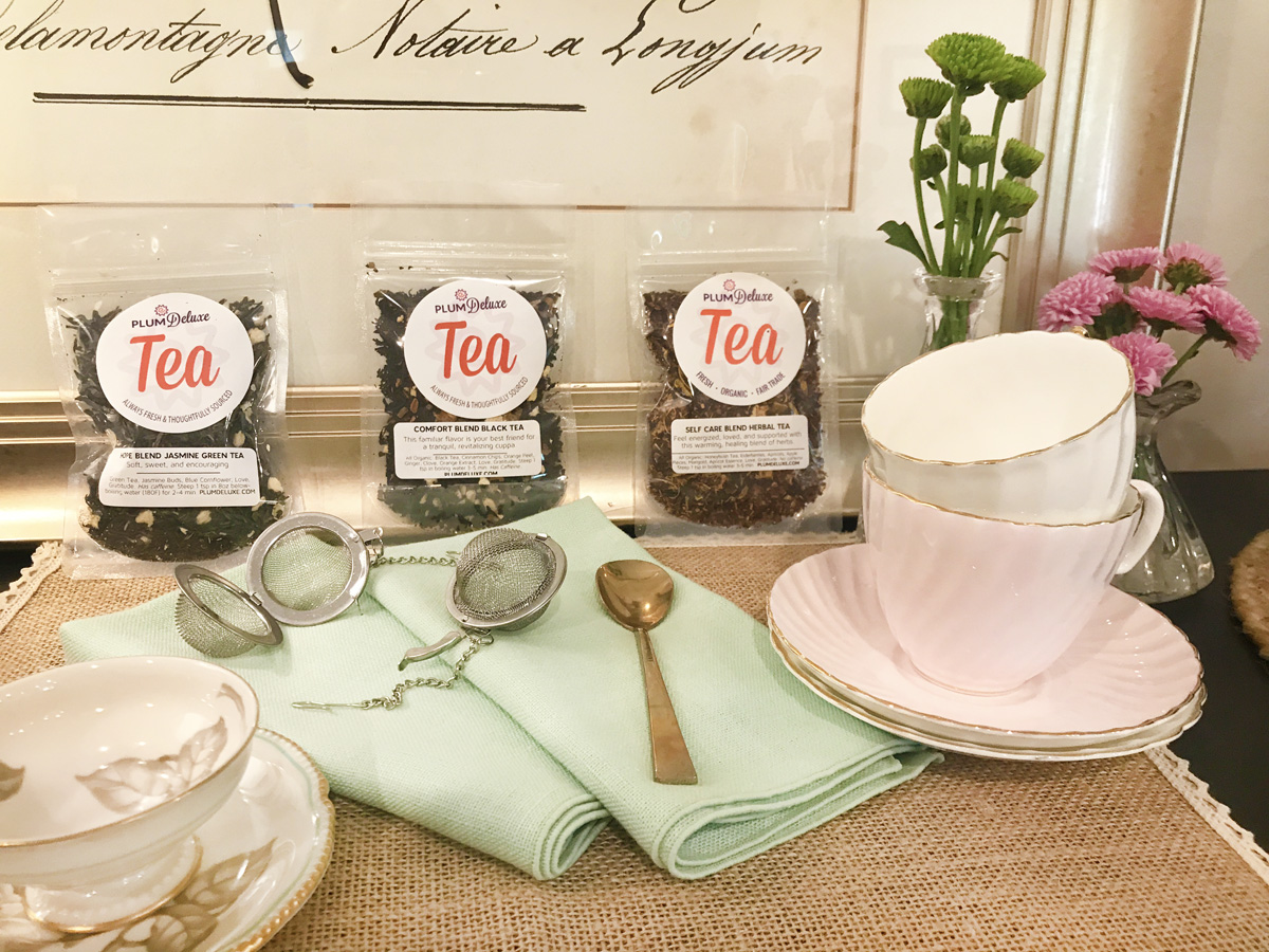 Three packages of Plum Deluxe loose leaf tea, three teacups with matching saucers, two mesh tea infusers, a teaspoon, and two mint green cloth napkins are arranged on a side table.