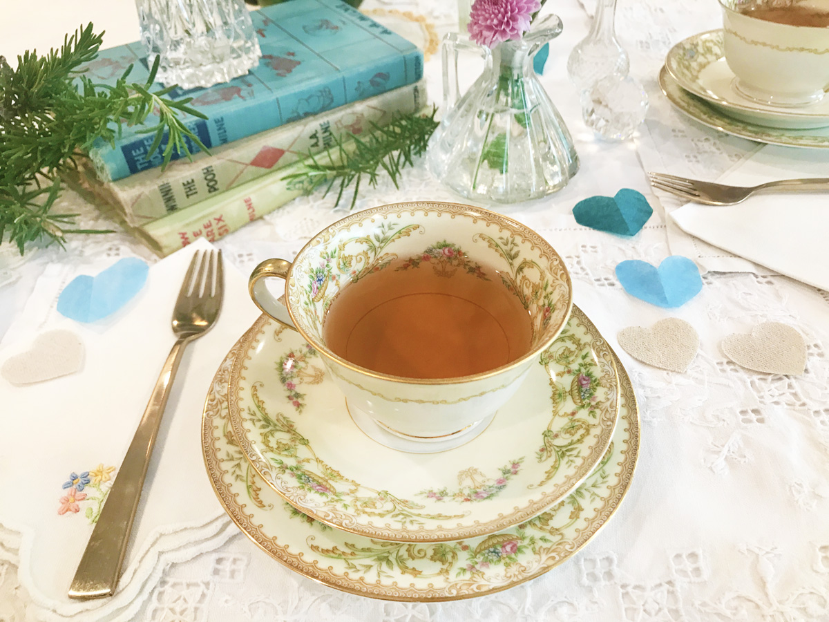 A white teacup with floral edging sits on a matching saucer on a white lace tablecloth. Surrounding it are a fork, cut out paper hearts in blue and beige, a stack of hardcover books in blue and beige, and a spring of fresh rosemary.