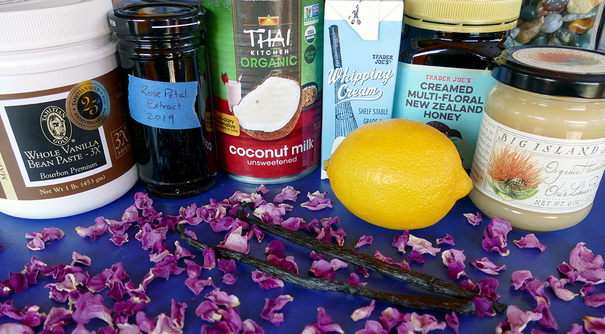 A group of tea additions sits on a blue surface, with varying bottles and boxes—whole vanilla bean paste, rose petal extract, coconut milk, whipping cream, New Zealand honey, and organic Hawaiian honey.