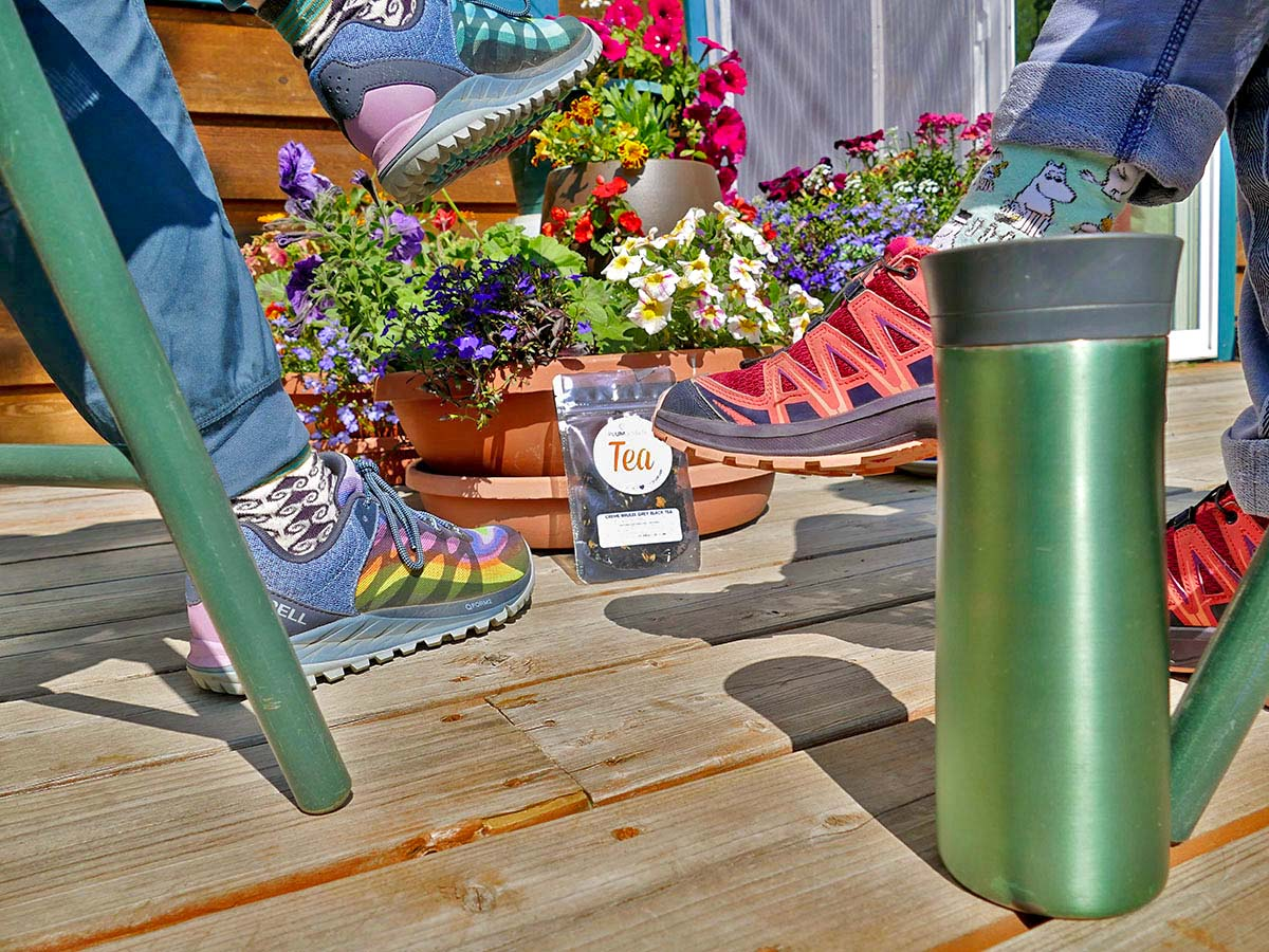 Two people sit on a deck, next to a mug of tea and a flower pot full of varying colorful flowers and a bag of earl grey tea sitting in front.