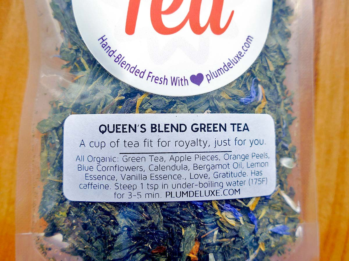 A bag of Queen's Blend green earl grey tea sits on a wooden background: a cup of tea fit for royalty, just for you!