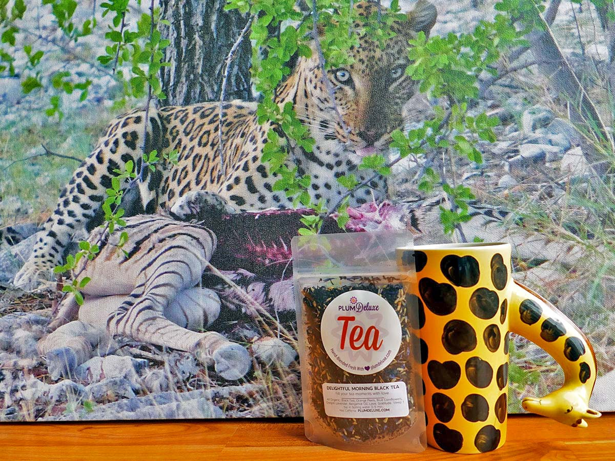 A giraffe-patterned mug sits next to a cup of Delightful Morning Earl Grey tea. A canvas of a leopard hiding in foliage can be seen in the background.