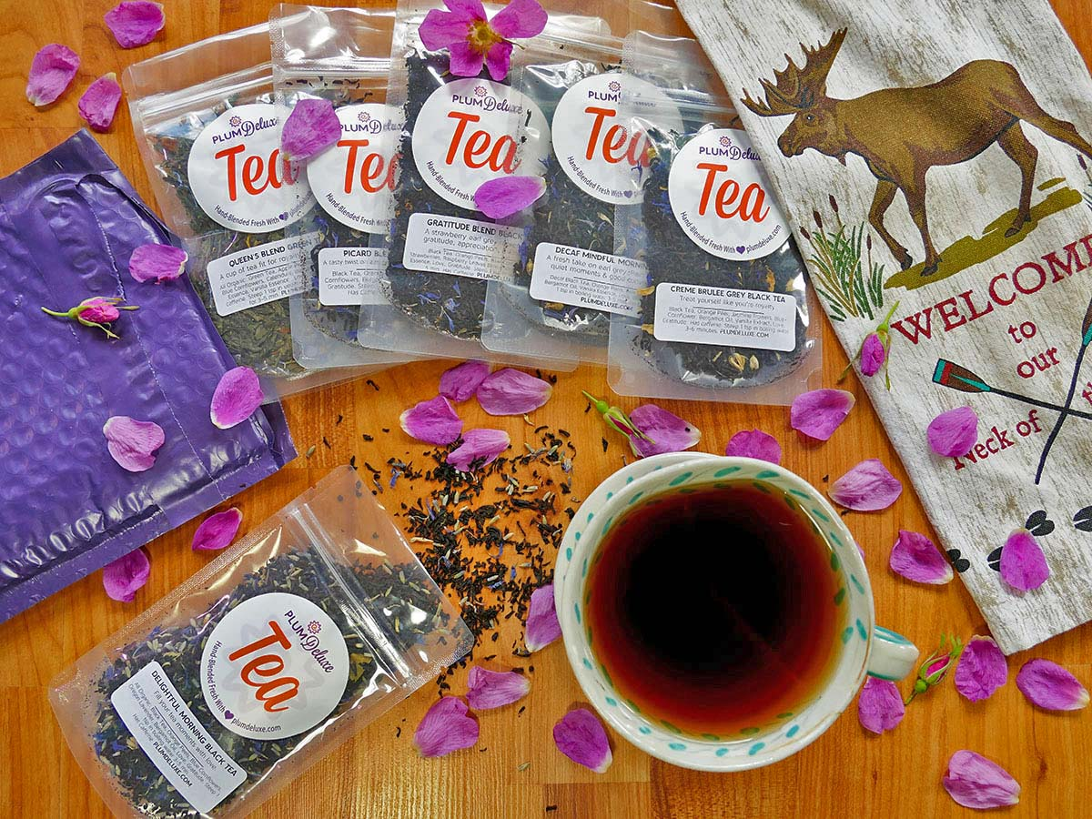 A variety of Earl Grey teas sit on a wooden background, with a purple mailer on the left and a tea towel with a moose on the right. A cup of tea sits just below them, with tea leaves and bright pink flower petals scattered around.