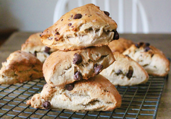Three chai chocolate chip scones are stacked on top of each other on a wire cooling rack.