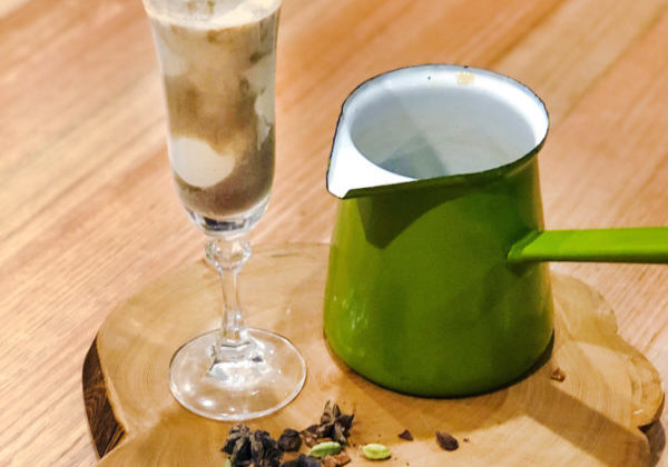 A tall glass of chai affogato sits on a wooden board next to a pile of chai spices and a green pitcher.