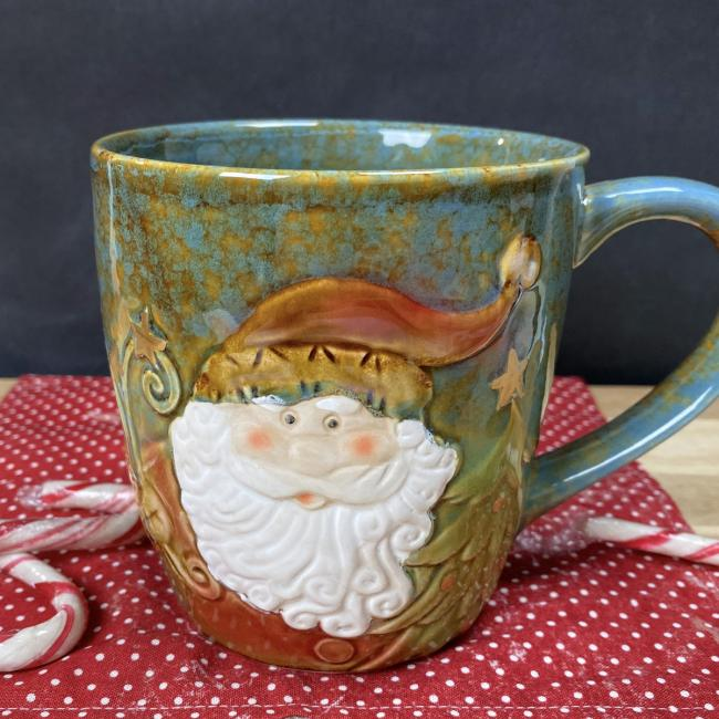 An earthenware mug featuring an image of Santa Claus sits on a red napkin surrounded by candy canes.
