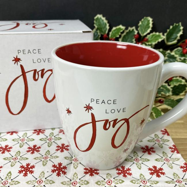 A white mug with the word JOY written in red across it sits on a red and white snowflake print napkin. A matching decorative gift box and bough of holly are in the background.
